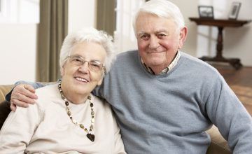 Elderly couple sat at home smiling